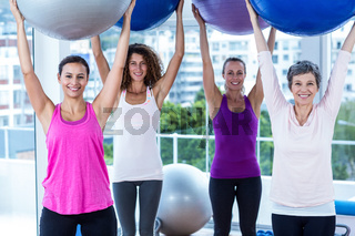 Portrait of cheerful women holding exercise balls with arms raised