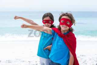 Siblings wearing superhero costume at beach