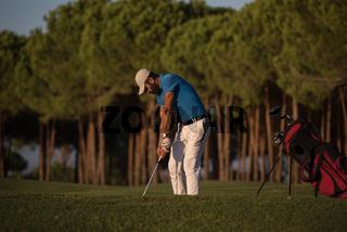 golfer hitting a sand bunker shot on sunset