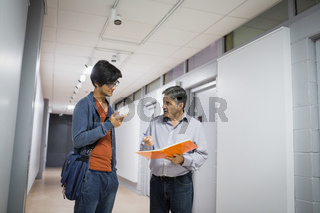 Professor with notebook talking to a student