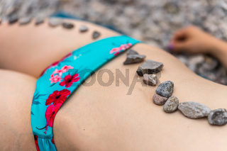 Pebble stones on the body of a young attractive woman, wellness