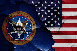 flags of United States Marshals Service and USA painted on cracked wall