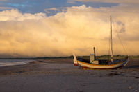 stranded colorful fishing boat on the beach in denmark after thunderstorm