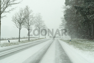 snow storm on a country road and dangerous road conditions in winter