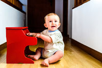 Smiling baby playing a toy piano while learning music.