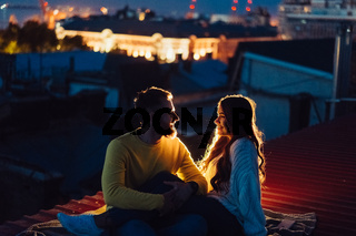 Loving couple is sitting on the roof of the house. Beautiful evening