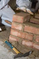 Craftsman builds brick wall - closeup bricklayer
