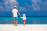 Adorable little girl and dad during tropical beach vacation