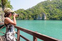 Woman tourist taking photos Thale Nai