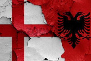 flags of England and Albania painted on cracked wall