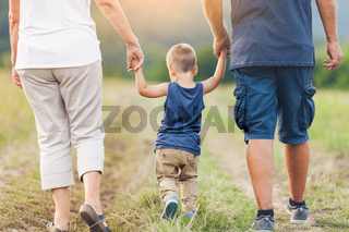 Happy grandparents on a walk outside with their grandchild