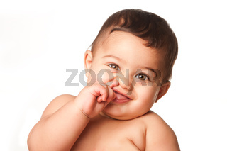 Cute baby infant with big green eyes picking nose on white