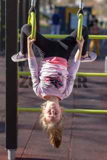 Young girl exercising on gymnastic rings upside down position