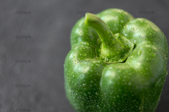 close up of green pepper on slate stone background