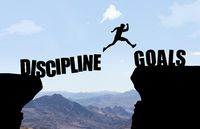 Man jumping over abyss with text Discipline/Goals in front of mountain background.
