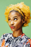 Stylish young girl with bleached curly hair looking up, in front of a green background