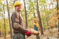 Zwei Forstarbeiter tragen Baumstamm bei Holzernte
