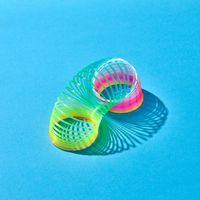 Toy plastic rainbow slinky with shadows on blue.