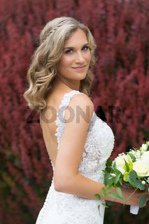 Wedding. Beautiful bride in white dress holding wedding bouquet.
