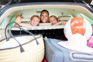 Mutter und zwei Kinder beim Auto fahren