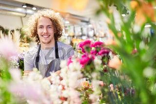 Lächelnder Florist zwischen bunten Schnittblumen