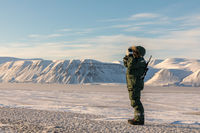 Man with a rifle and binoculars looks out on the horizon in arctic landscape at Svalbard
