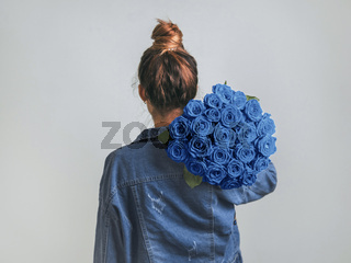 Back view of woman, holding Classic Blue roses