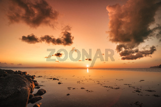 Sunrise over the sea by the shore with rocks