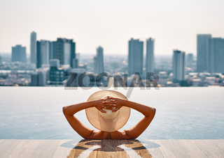 Back view of young woman in hat relaxing in swimming pool on the roof top of hotel and enjoy cityscape