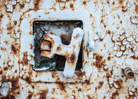 The lock on the old iron trailer - Old age, vintage, metal corrosion, layers of old peeling paint of different colors