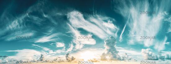 panorama of blue cloudy sky and rising sun