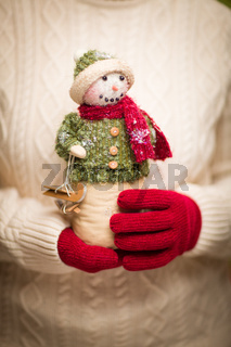 Woman Wearing Seasonal Red Mittens Holding Christmas Snowman
