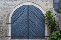Blue wooden gate in natural stone facade