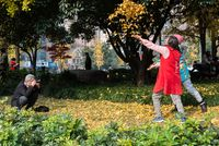 Senior man taking photos of two women throwing yellow gingko tree leaves