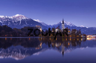 Bled lake at winter night with stars and reflection