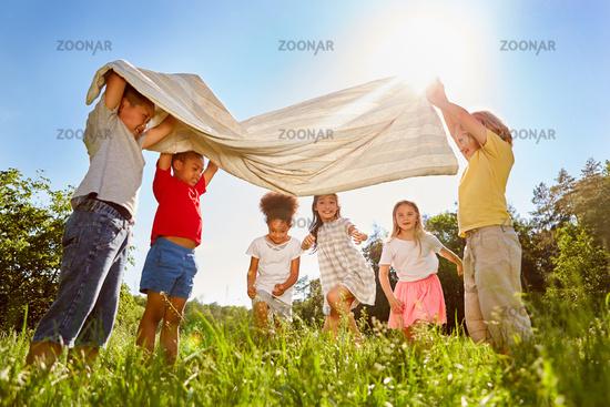 Gruppe Kinder spielt zusammen mit einem Tuch