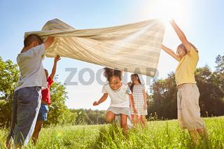 Kinder im Ferienlager spielen mit einem Tuch