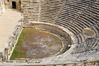 Ancient antique amphitheater in city of Hierapolis in Turkey. Steps and antique statues with columns in the amphitheater