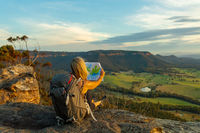 Hiker or tourist sitting on a rock using a map