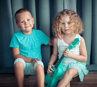 Portrait of a cute kids with ukulele