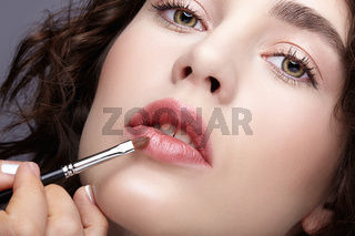 Make-up artist apply beauty makeup on the lips of a beautiful girl. Visagist with makeup brush in hand