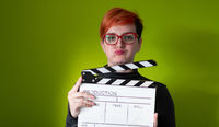 redhead woman holding movie  clapper on green background