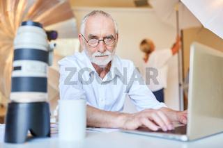 Älterer Fotograf am Laptop bei der Bildbearbeitung