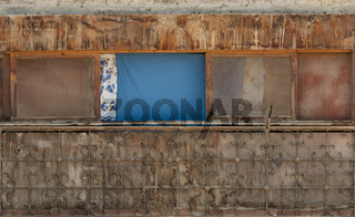 Old weathered shack with dirty windows and cloth curtains on sunny day in village