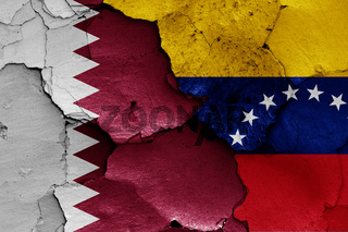 flags of Qatar and Venezuela painted on cracked wall