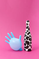 Balloon rubber glove with painted white bottle with black spots.