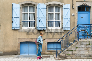 teenage girl dressed in blue interacting with her cell phone in front of a house with blue shutters and doors