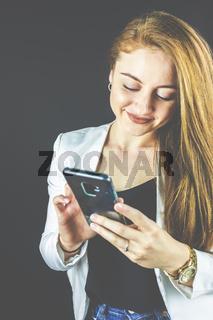 Junge Frau mit Jeans und weißem Blazer lächelt und hält Ihr Smartphone in der Hand, telefoniert und