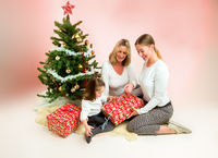 Grandmother with adult daughter and grandchild. under the christmas tree, opening presents