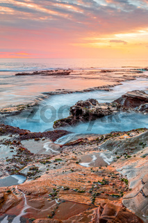 Ocean flowing into coastal channels eroded into rock and a stunning sunrise